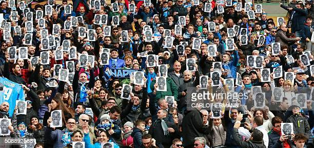 TOPSHOT People hold flyers depicting the face of Napoli's French defender Kalidou Koulibaly before the Italian Serie A football match SSC Napoli vs...