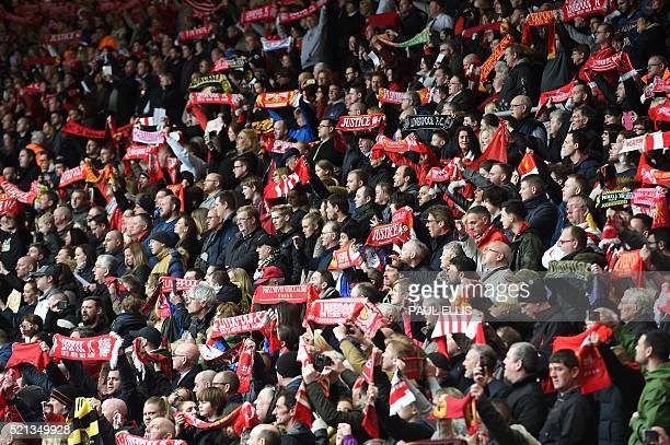 People hold football scarves during a memorial service at Anfield in Liverpool north west England on April 15 on the 27th anniversary of the...