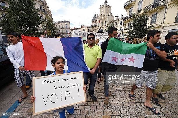 People hold French and Syrian national flags as hundreds of demonstrators protest against the mayor of the city and to support Syrian refugees on...