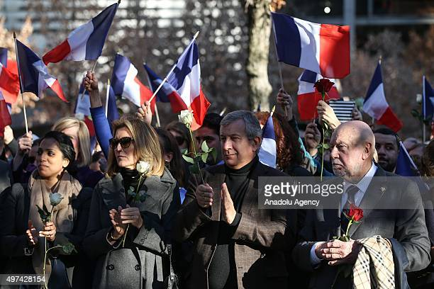 People hold French flags and flowers as they hold a memorial service for the Paris terror attakcs victims under the Survivor Tree the National...