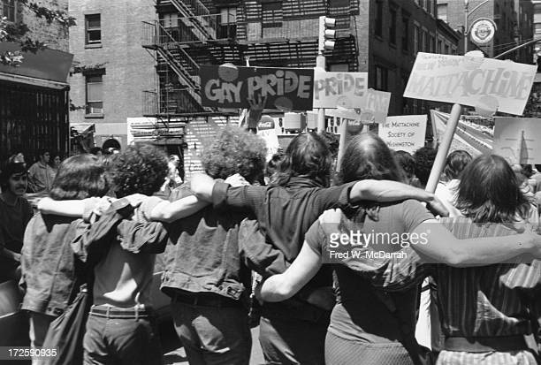 People hold 'Gay Pride' and 'Mattchine' signs during the first Stonewall anniversary march then known as Gay Liberation Day as they parade arm in arm...