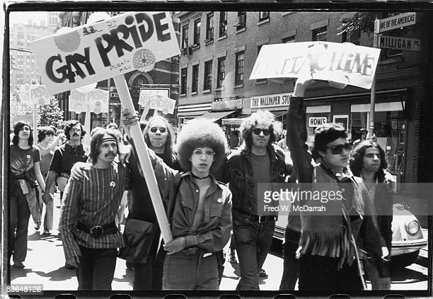 People hold 'Gay Pride' and 'Mattchine' signs during the first Stonewall anniversary march then known as Gay Liberation Day as they parade along 6th...