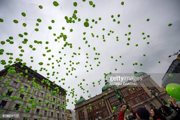 People hold green ballons to mark the International Childhood Cancer Day during a rally organised by the National Association of Parents of Children...