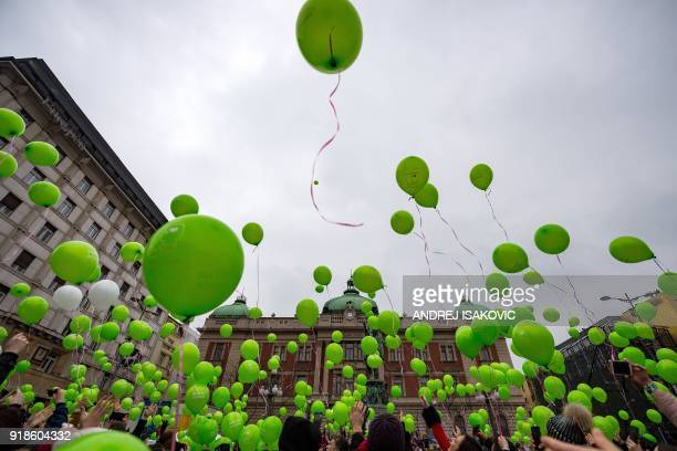 TOPSHOT People hold green ballons to mark the International Childhood Cancer Day during a rally organised by the National Association of Parents of...