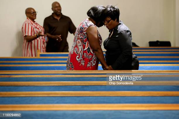 People hold hands and pray following a memorial service for the 12 victims of a mass shooting at Piney Grove Baptist Church June 02, 2019 in Virginia...