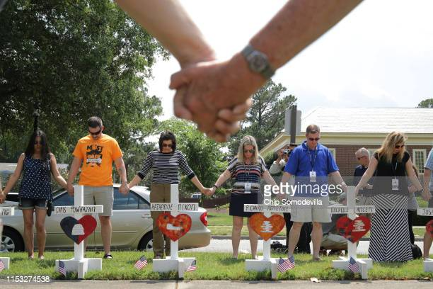 People hold hands and pray together at a makeshift memorial for the 12 victims of a mass shooting at the Municipal Center June 02 2019 in Virginia...