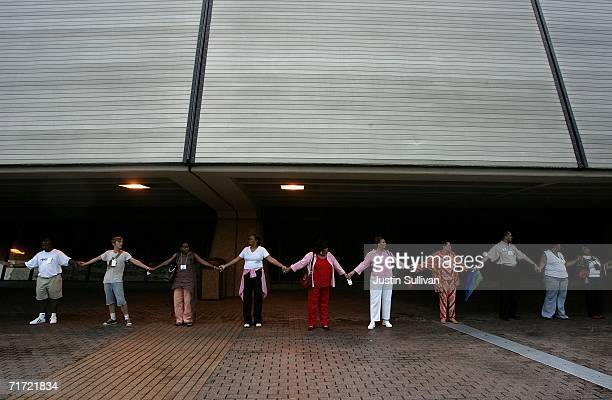 People hold hands as the create a human chain to circle the Louisiana Superdome August 26 2006 in New Orleans Louisiana People held hands and...