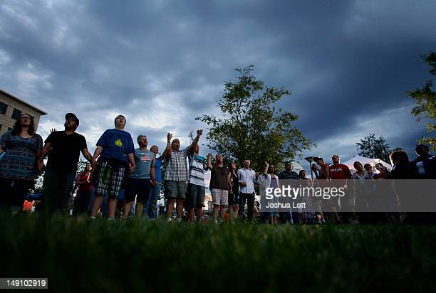 People hold hands as they pray during a memorial service outside the Aurora Municipal Center July 22 2012 in Aurora Colorado The memorial was for the...