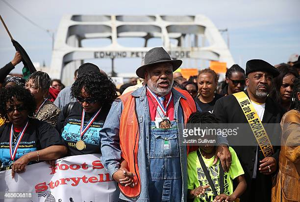 People hold hands as they walk across the Edmund Pettus Bridge during the 50th anniversary commemoration of the Selma to Montgomery civil rights...