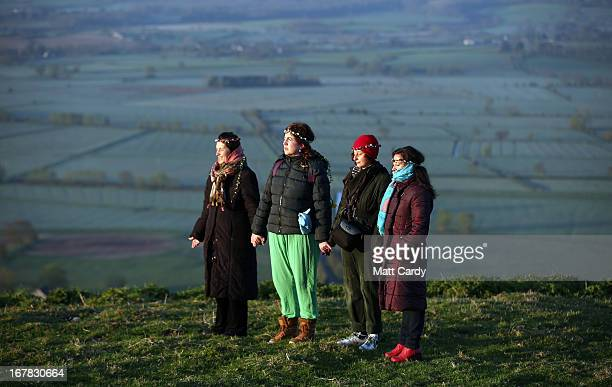 People hold hands as they watch the sun rise as they join in a Beltane dawn celebration service in front of St Michael's Tower on Glastonbury Tor on...