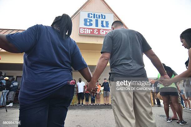 People hold hands during a moment of prayer during a small memorial service outside Club Blu where two people were killed and at least 15 were...