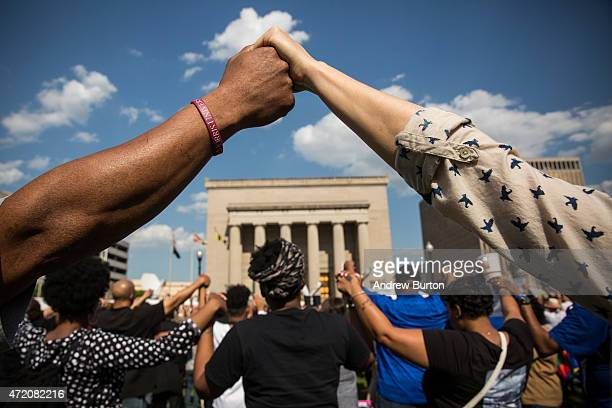People hold hands during a rally lead by faith leaders in front of city hall calling for justice in response to the death of Freddie Gray on May 3...