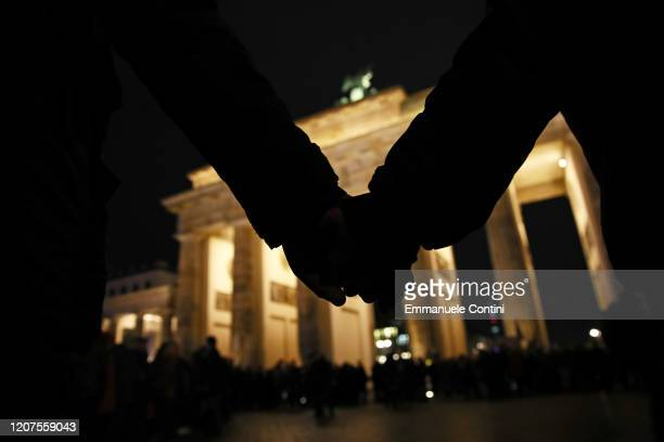 People hold hands during a vigil at the Brandenburg Gate to commemorate the victims of the Hanau shootings on February 20 2020 in Berlin Germany A...