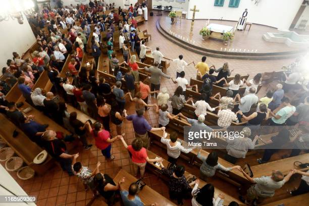 People hold hands during a vigil for victims at St Pius X Church, after a mass shooting which left at least 20 people dead, on August 3, 2019 in El...
