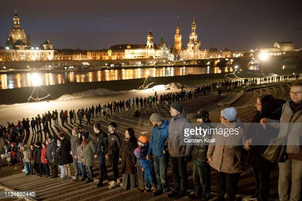 People hold hands in a human chain to commemorate the 74th anniversary of the firebombing of the city during World War II on February 13 2019 in...