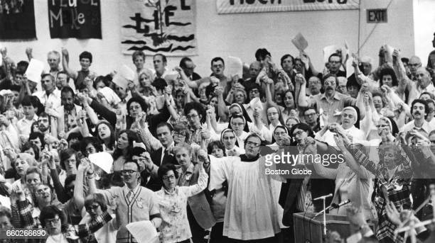 People hold hands in prayer as they sing hymns of praise at Boston College's Roberts Center in Newton MA on Jun 6 1976