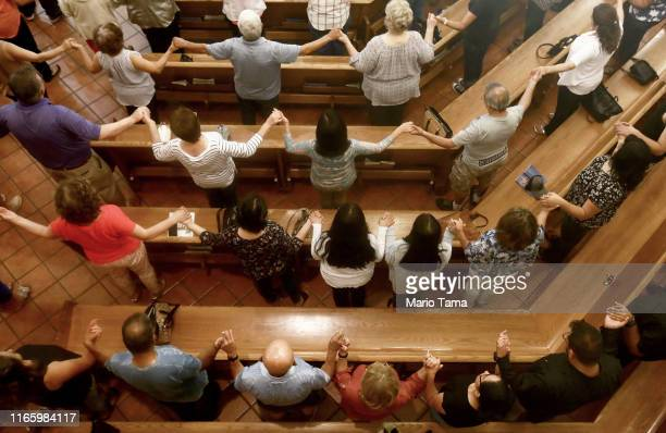 People hold hands in St Pius X Church at a vigil for victims after a mass shooting which left at least 20 people dead on August 3 2019 in El Paso...