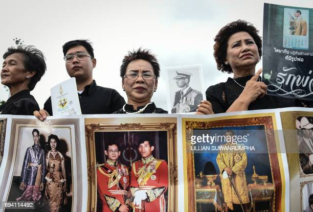 People hold images of Thai king Maha Vajiralongkorn with his father the late king Bhumibol Adulyadej before a Buddhist ceremony at the King Rama V...