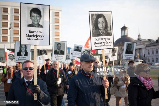People hold images of victims of a plane crash during celebrations of anniversary of presidental plane crash near Smolensk in Warsaw on April 10 2019