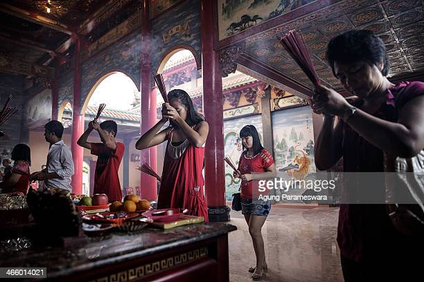 People hold incense sticks as they attends prayers during Chinese New Year celebrations for the Year of The horse at Satya Dharma Temple on January...