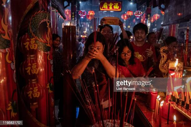 People hold incense sticks as they pray during Lunar New Year's Eve celebrations at Fuk Ling Miau temple on January 24, 2020 in Yogyakarta,...