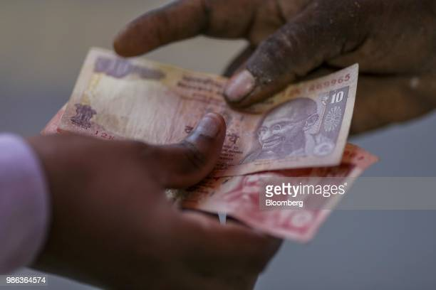 People hold Indian rupee banknotes for a photograph in Mumbai India on Thursday June 28 2018 The Indianrupeeslumped to an alltime low as a...