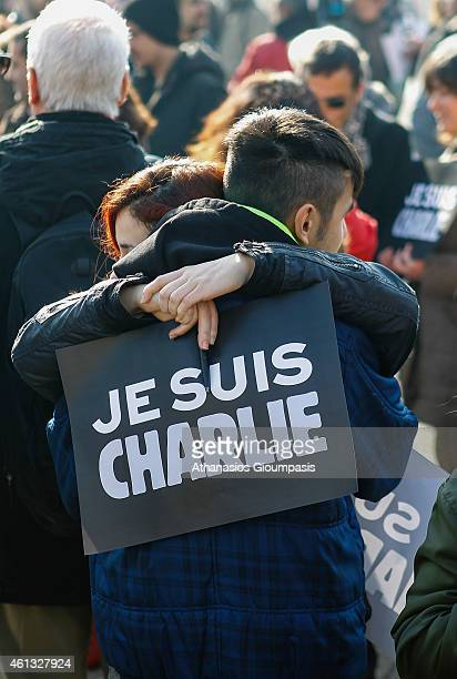 People hold 'Je Suis Charlie' placards pencils and pens as they gather at a vigil to show support for the victims of the French terror attacks in...