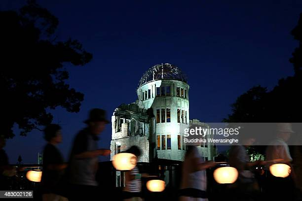 People hold lanterns as they walk to wish for peace in front of the Atomic Bomb Dome at the Hiroshima Peace Memorial Park on the day before the 70th...