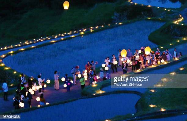 People hold lanterns march on among the Sakaori rice terrance where some 1000 candles are illuminated on June 2 2018 in Ena Gifu Japan