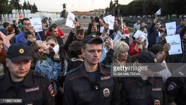 People hold leaflets reading For anyone except Beglov after the name of Saint Petersburg's acting city chief as policemen stand at the ready to block...