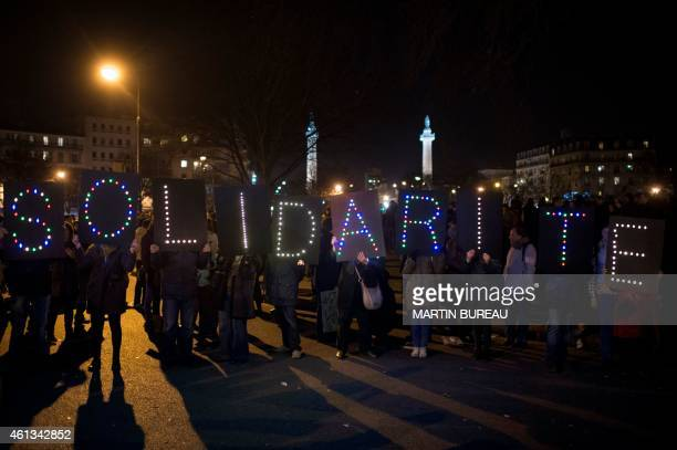 People hold letters to form the word solidarity during the Unity rally Marche Republicaine on January 11 2015 in Paris in tribute to the 17 victims...