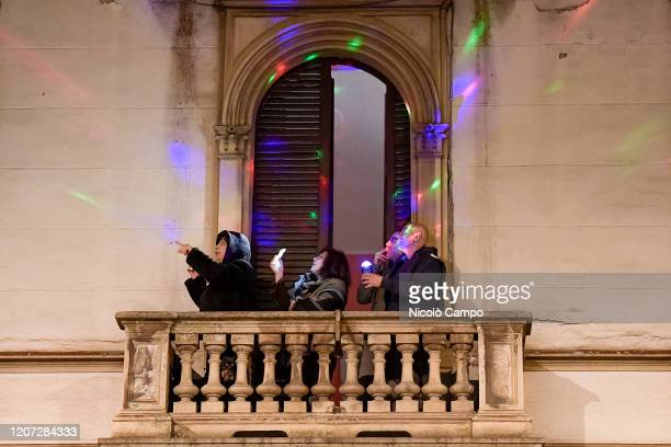 People hold lights on their balcony during a flash mob launched throughout Italy to bring people together. The Italian government imposed...