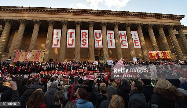 People hold Liverpool football scarves in the air as they sing 'You'll Never Walk Alone' outside St George's Hall in Liverpool north west England on...