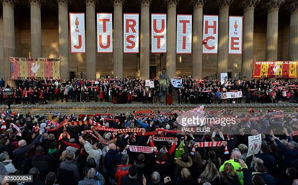 People hold Liverpool football scarves in the air as they sing You'll Never Walk Alone outside St George's Hall in Liverpool north west England on...