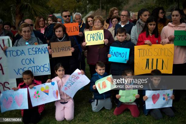 People hold messages of support as rescue workers continue efforts to find a boy who fell down a well in Totalan in southern Spain on January 16 2019...