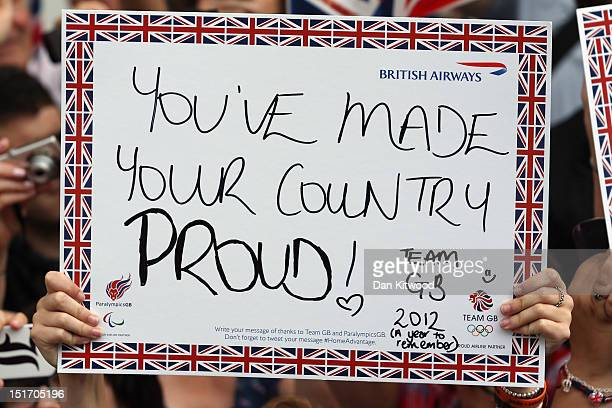 People hold messages of support during the London 2012 Victory Parade for Team GB and Paralympic GB athletes on September 10 2012 in London England