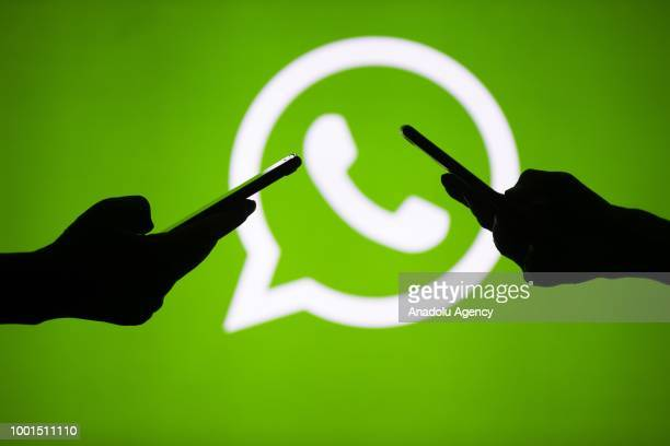 People hold mobile phones in front of the logo of WhatsApp application in Ankara Turkey on July 18 2018