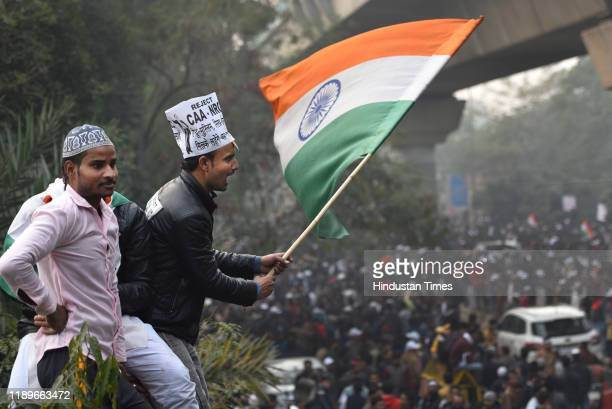 People hold national flag during a protest against the new citizenship law which was recently passed in both houses of the parliament at Jamia Millia...