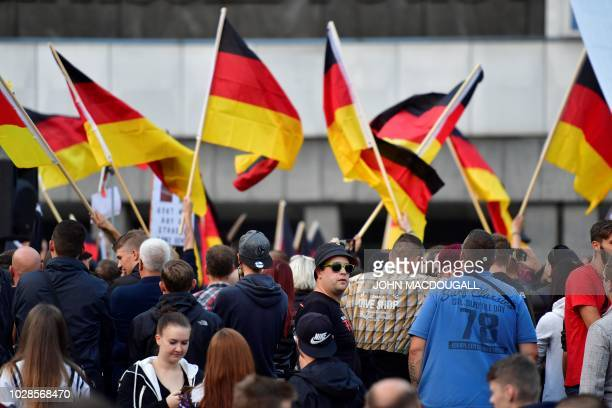 """People hold national flags during a march organised by the right-wing populist """"Pro Chemnitz"""" movement, on September 7, 2018 in Chemnitz, the..."""