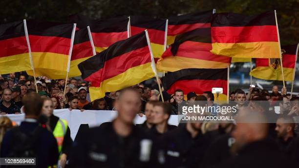"People hold national flags during a march organised by the right-wing populist ""Pro Chemnitz"" movement, on September 7, 2018 in Chemnitz, the..."