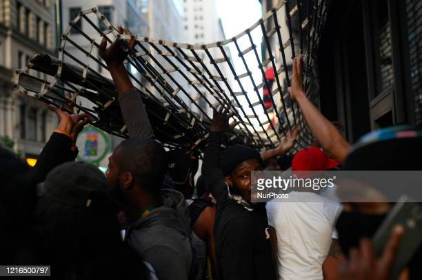People hold open a metal gate to gain access to a store on Walnut Street in Philadelphia PA on May 30 2020 Protestors clash with police in cities...