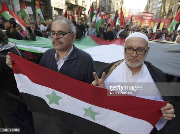 People hold Palestinian flags as they take part in a protest against the visit of Israeli Prime Minister Benjamin Netanyahu in front of the Israeli...