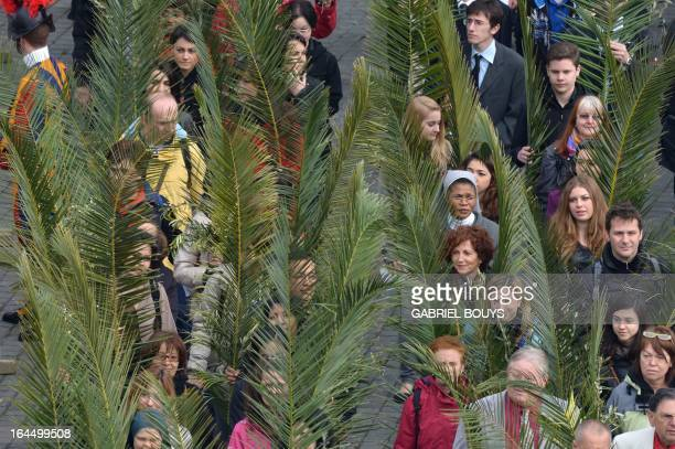 People hold palms as they arrive in St Peter's square to attend a papal mass as part of the Palm Sunday celebration on March 24 2013 at the Vatican...