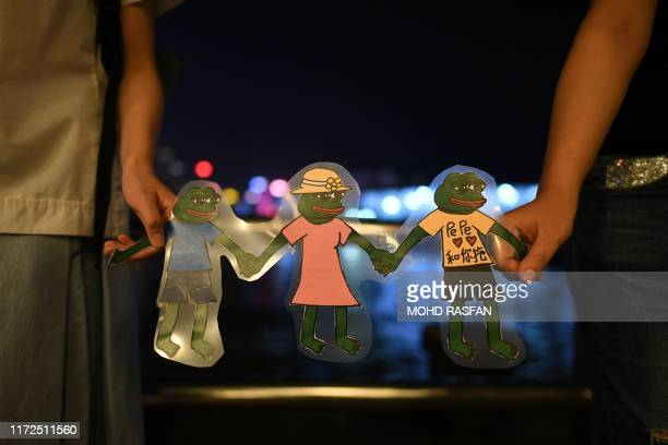 """People hold Pepe the Frog"""" meme, a character used during the pro-democracy protesters in the harbour area in Hong Kong on September 30, 2019. -..."""