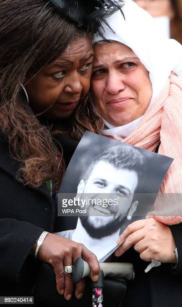 People hold photos and flowers as they leave the Grenfell Tower National Memorial Service held at St Paul's Cathedral on December 14 2017 in London...