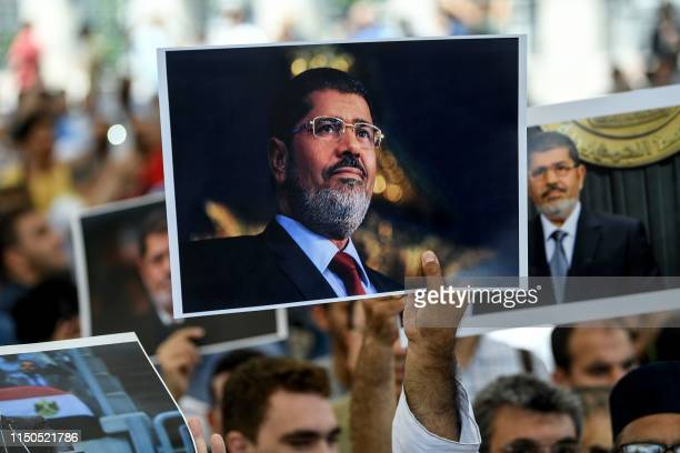 TOPSHOT People hold picture of Egyptian President Mohamed Morsi during a symbolic funeral cerenomy on June 18 2019 at Fatih mosque in Istanbul...