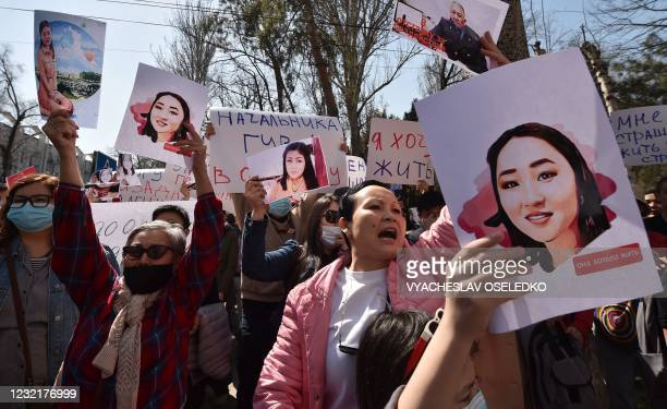People hold pictures as they attend a rally for women's rights protection in Bishkek, on April 8, 2021. - Hundreds of people rallied in Kyrgyzstan's...