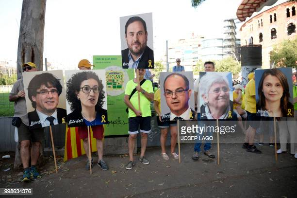 People hold pictures of Catalan leaders in jail or exiled Carles Puigdemont Marta Rovira Oriol Junqueras Jordi Turull Clara Ponsati and Meritxell...