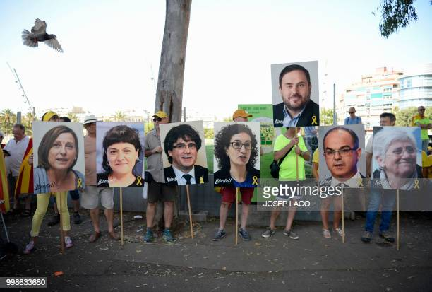 TOPSHOT People hold pictures of Catalan leaders in jail or exiled Carme Forcadel Anna Gabriel Carles Puigdemont Marta Rovira Oriol Junqueras Jordi...