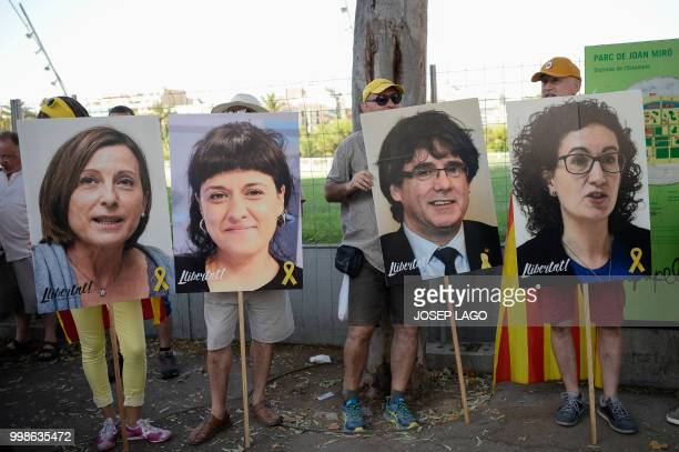 People hold pictures of Catalan leaders in jail or exiled Carme Forcadel Anna Gabriel Carles Puigdemont and Marta Rovira during a demonstration in...
